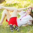 Outdoor portrait young woman with long brown hair. The girl floral accessories, she poses lying on the grass in the park — Stock Photo #50615013
