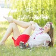 Outdoor portrait young woman with long brown hair. The girl floral accessories, she poses lying on the grass in the park — Stock Photo #50615029