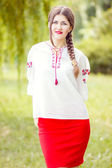 Outdoor fashion brown hair woman portrait in embroidered Ukrainian national costume. Beautiful woman with bright makeup posing on the nature — Stock Photo