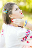 Outdoor portrait young woman with long brown hair. The girl floral accessories, she poses lying on the grass in the park — Стоковое фото