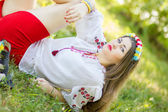 Outdoor portrait young woman with long brown hair. The girl floral accessories, she poses lying on the grass in the park — Stock Photo