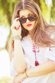 Portrait of a beautiful young woman with long brown hair who poses with sunglasses. The girl is on the nature and smiling. — Stock Photo