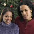Portrait of couple in front of Christmas tree — Stock Photo #13221269