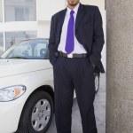 Hispanic car salesman next to new car — Stock Photo #13223459