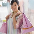 Chinese woman holding shopping bags — Stock Photo #13225141