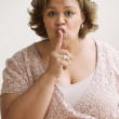 Middle-aged overweight Hispanic woman with her index finger up to her pursed lips — Stock Photo #13228277