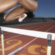 Female track athlete clearing a hurdle — Stok fotoğraf