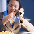 African businesswoman eating popcorn - Foto Stock