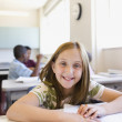 Girl smiling at desk in classroom — Stock Photo