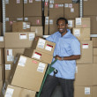 Male African warehouse worker using hand truck — Stock Photo
