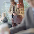 Businesswoman with to go coffee looking in purse at cafe — Stock Photo #13220627
