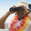Senior Africmlooking through binoculars at beach — Stock Photo #13220648