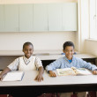 Two young boys smiling at desk in classroom — Stock Photo