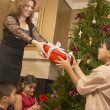 Hispanic woman giving son Christmas gift — Stock Photo