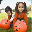 Young girls holding pumpkin buckets - Stock Photo