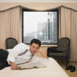 Asibusinessmreading newspaper in hotel room — Stock Photo #13220702