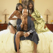Man in bed with two women - Stock Photo
