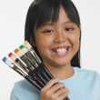 asian girl holding paintbrushes with different colors on bristles — Stock Photo