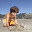 Boy building sandcastle at beach — Stock Photo