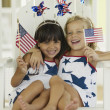 Portrait of two young girls with American flags — Stock Photo