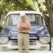 Portrait of elderly man standing in front of old pickup truck — Stock Photo