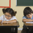 Stock Photo: Children writing at desks in classroom