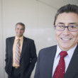 Portrait of Hispanic businessman with coworker in background — Stock Photo
