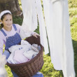 Stock Photo: Pacific Islander girl with laundry basket next to clothesline