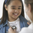 Female doctor listening to young girl&#039;s heartbeat - Stock Photo