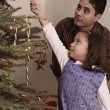 Hispanic girl hanging candy cane on Christmas tree — Stok fotoğraf