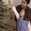 Hispanic girl hanging candy cane on Christmas tree - Stock Photo