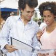 Stock Photo: Young couple examining a menu