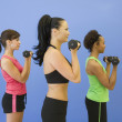 Multi-ethnic women lifting weights — Stock Photo