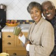 Royalty-Free Stock Photo: Senior African couple hugging in kitchen