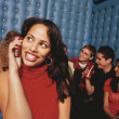 Young woman taking cell phone call in night club — Stock Photo