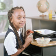 School girl eating a packed lunch at her desk — Stock Photo