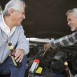 Two senior men working under hood of car — Stock Photo #13221044