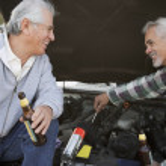 Two senior men working under hood of car — Stock Photo