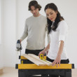 Stock Photo: Hispanic couple measuring wood