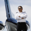 Stock Photo: Asian male pilot standing at tail of private airplane