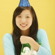 Portrait of womwearing birthday hat and holding wrapped gift — Stock Photo #13221100