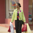 Woman crossing street with shopping bags — Stock Photo