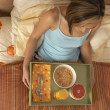 High angle view of woman eating breakfast in bed — Stock Photo
