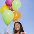 Asian girl holding bunch of balloons — Stock Photo