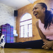 Woman stretching on floor while laughing - ストック写真