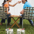 Multi-ethnic couple eating near newly painted fence — Stock fotografie