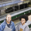 Two men standing in front of conveyor belt — Stock Photo