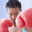 African American woman wearing boxing gloves - Stock Photo