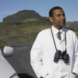 Stock Photo: Min lab coat with binoculars in deserted rural area