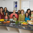 Large Hispanic family in kitchen with food — Foto Stock